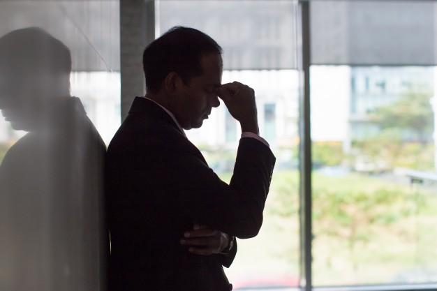 homem encostado na parede com a cabeça baixa, apoiada nas mãos, demonstrando stress